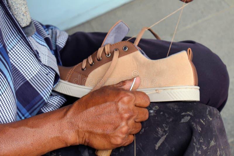Процесс ручной репарации, подошвы и ранта ботинка фиксируя и шить стоковые изображения