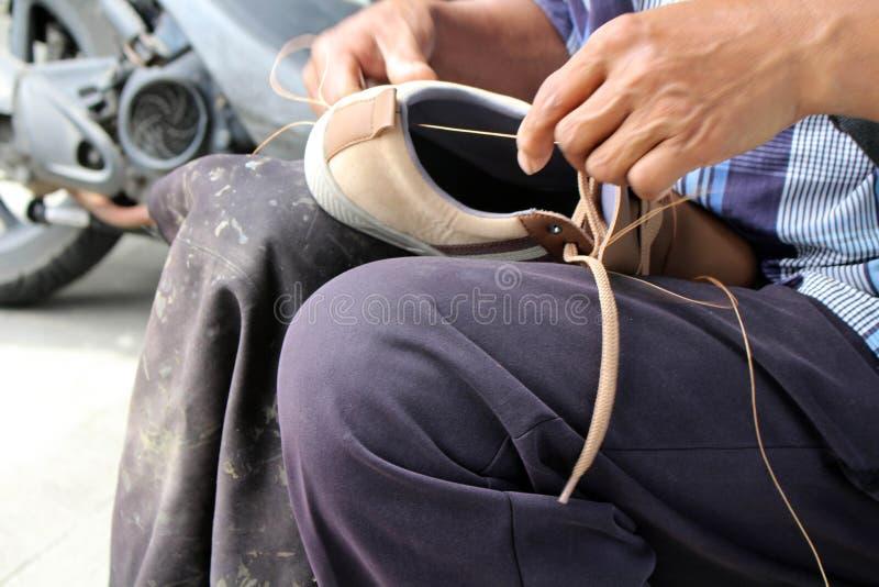 Процесс ручной репарации, подошвы и ранта ботинка фиксируя и шить стоковое фото rf