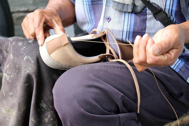 Процесс ручной репарации, подошвы и ранта ботинка фиксируя и шить стоковое фото