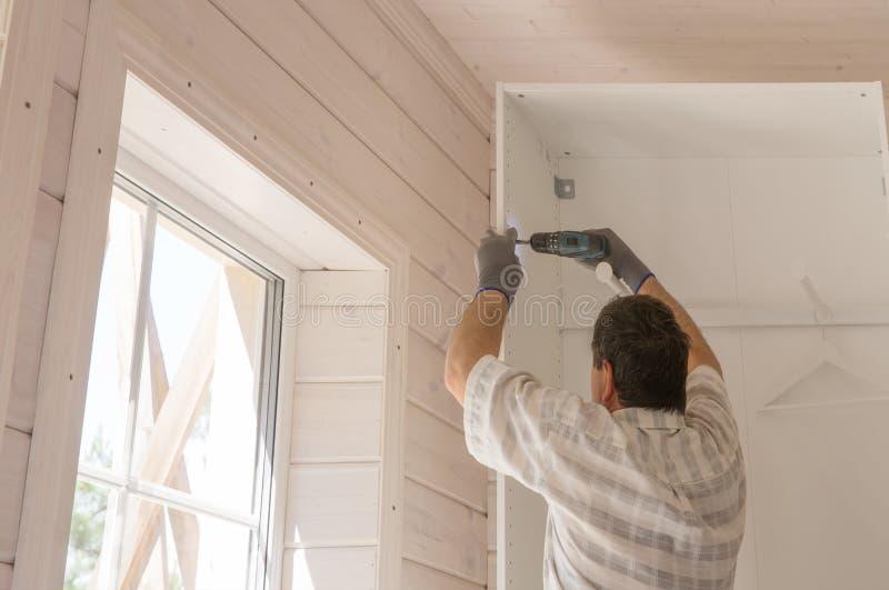 Процесс собирать мебель, мастер собирает белый шкаф используя электрический сверлильный аппарат в комнате с белым стоковое фото rf