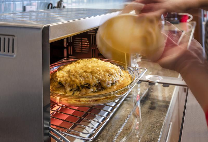 Повар льет соус в пирог мяса с грибами и пекут овощи и сыр в стеклянном лотке на решетке в электрической печи стоковые изображения