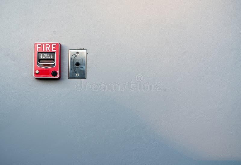 Пожарная сигнализация на белой бетонной стене Предупреждение и система безопасности Аварийное оборудование для сигнала тревоги бе стоковая фотография