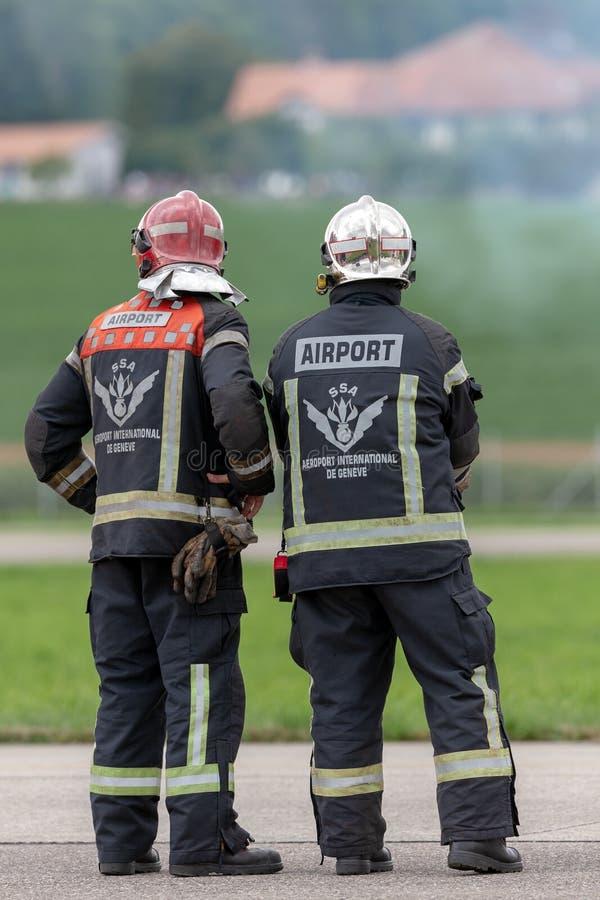 Пожарные аэропорта Женевы стоя на гудронированном шоссе аэропорта стоковые изображения rf