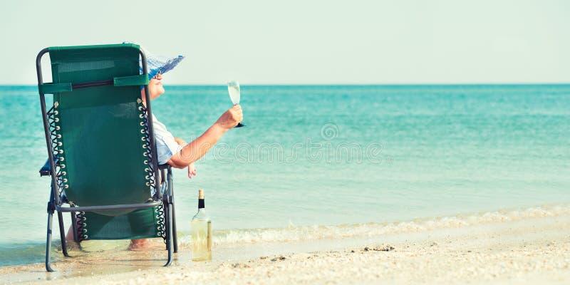Пожилая женщина сидит на пляже на шезлонге и выпивая вине стоковое изображение