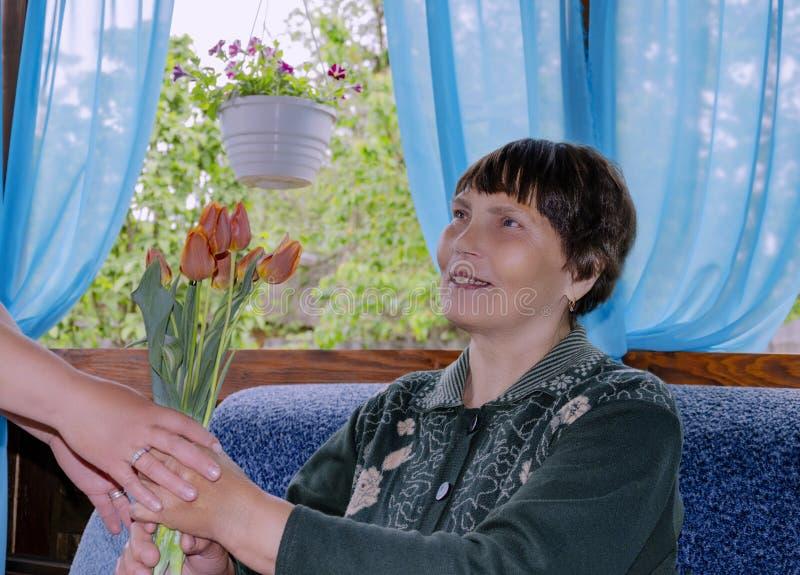 Пожилая женщина счастливо принимает букет тюльпанов стоковое фото rf