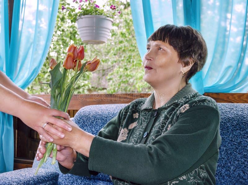 Пожилая женщина счастливо принимает букет тюльпанов стоковое изображение rf
