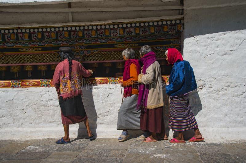 Пожилые женщины свертывая колеса молитве, stupa Chorten Kora, район Trashiyangtse, восточный Бутан стоковые изображения