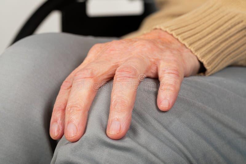 Пожилые руки на колене стоковые фото