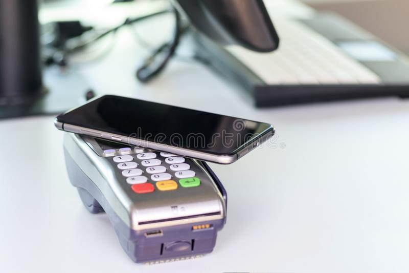 Покупатель, оплата через терминал POS мобильный телефон как карта банка там тонизируют стоковые фотографии rf