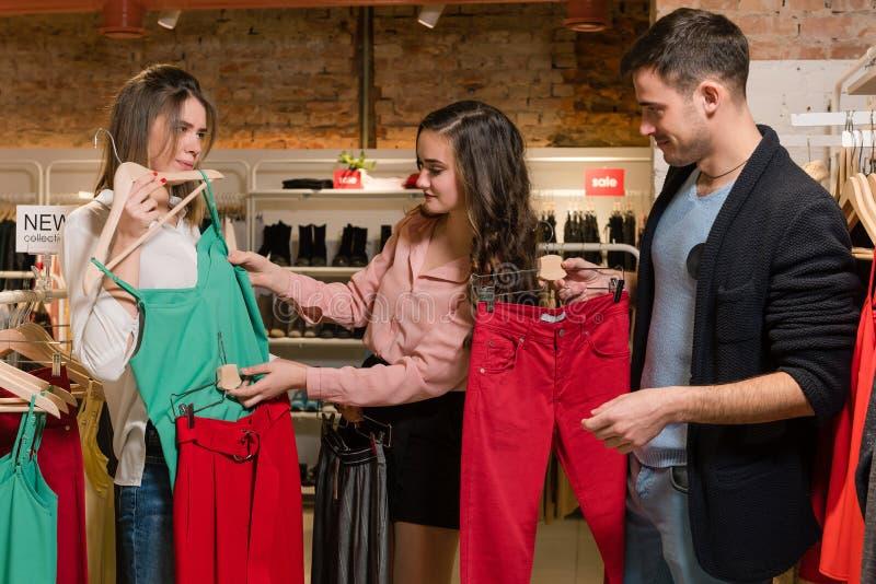 Покупки 2 женщин в магазине одежд моды стоковое фото rf