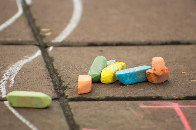 Покрашенный мел лежит на мостовой рядом с чертежом детей, творческими способностями детей стоковое фото