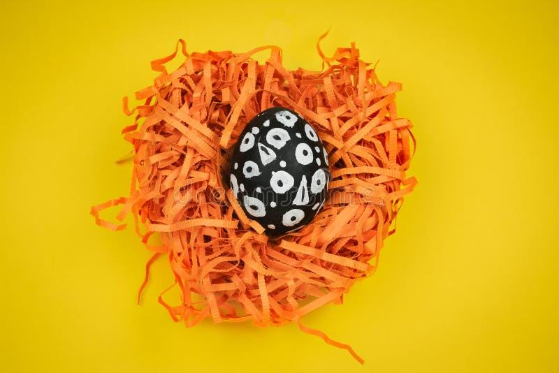 Покрашенное черно-белое пасхальное яйцо с геометрическим patetrn в декоративном гнезде на желтой предпосылке стоковое фото rf