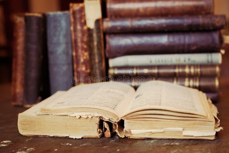 Полка книг со старой открытой книгой стоковые фотографии rf