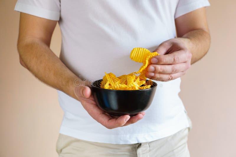 Полный человек есть картофельные чипсы жиреть стоковое фото rf