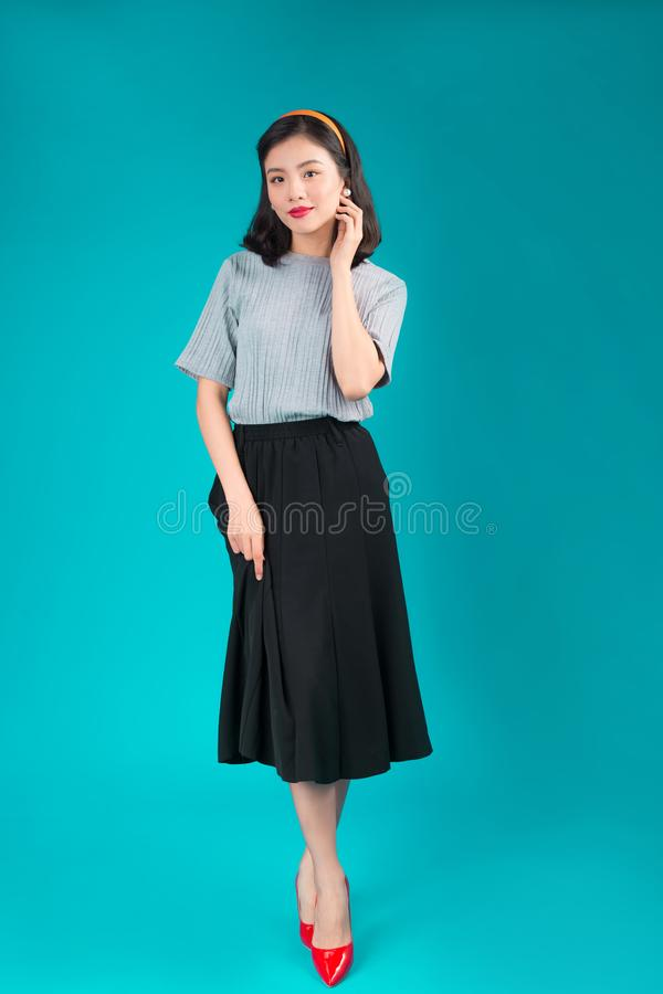 Полное тело усмехаясь азиатской женщины одело в платье стиля штыря-вверх над синью стоковое изображение rf