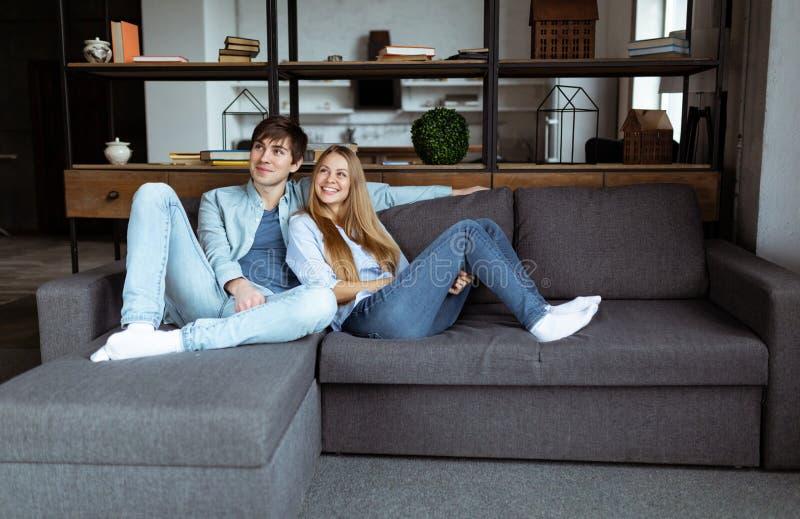 Полноразмерный портрет привлекательных ультрамодных пар сидя в современной квартире открытого пространства стоковые изображения rf