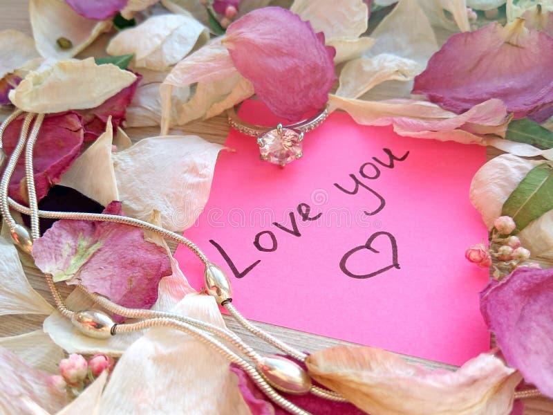 Полюбите вас сообщение на розовом липком примечании с сухими лепестками цветка розы и орхидеи и кольцом и цепью ювелирных изделий стоковая фотография rf