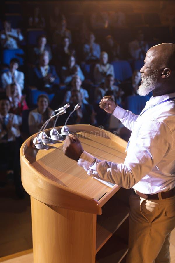 Положение бизнесмена около подиума и речи давать аудитории в аудитории стоковые фото