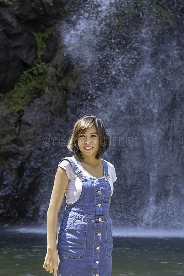 Положение женщины портрета азиатское в воде и насладиться водопадами ChokKra-Dinна Kanchanaburi в Таиланде стоковые изображения rf