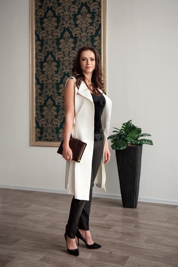Положение предпринимателя дамы в случайном деловом костюме с дневником в ее руках стоковые изображения