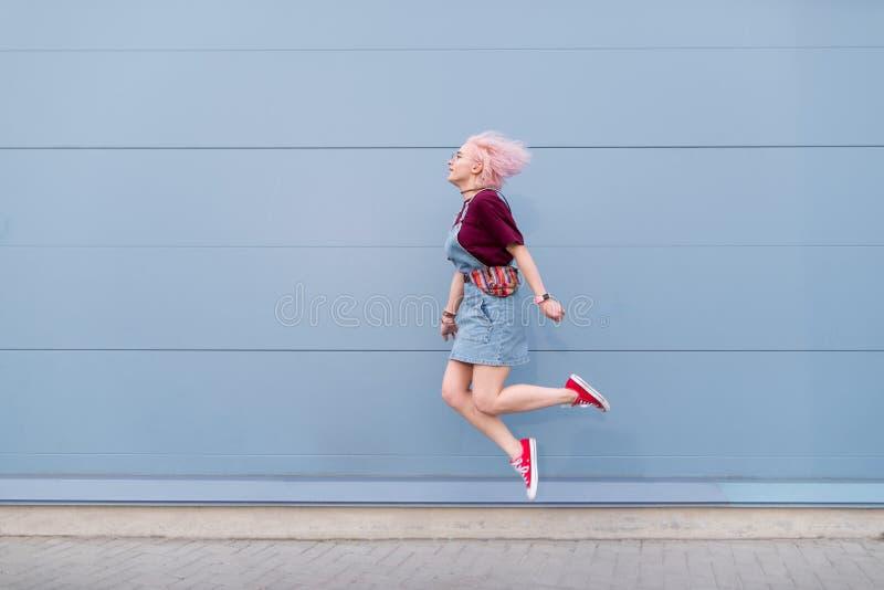 Положительная девушка в стильных одеждах скача на фоне голубой стены женщина скача на голубую предпосылку стоковая фотография