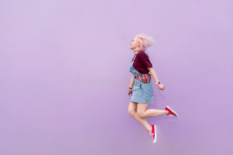 Положительная девушка в стильных одеждах скача на фоне пурпурной стены стоковая фотография