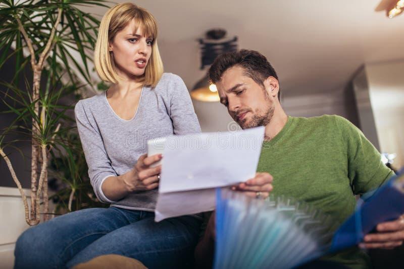 Положительные молодые пары обнимая и высчитывая счеты дома стоковое изображение rf