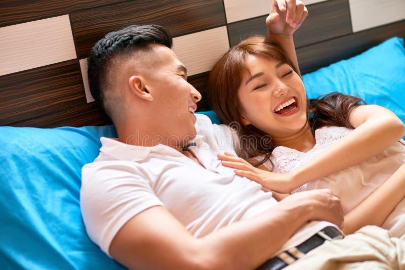 положите детенышей в постель пар счастливых стоковая фотография rf