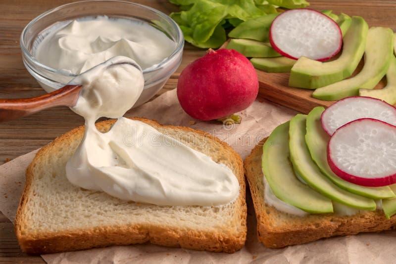 Подготовка тоста с йогуртом, авокадоом и редиской конец вверх сфокусируйте мягко стоковые фотографии rf