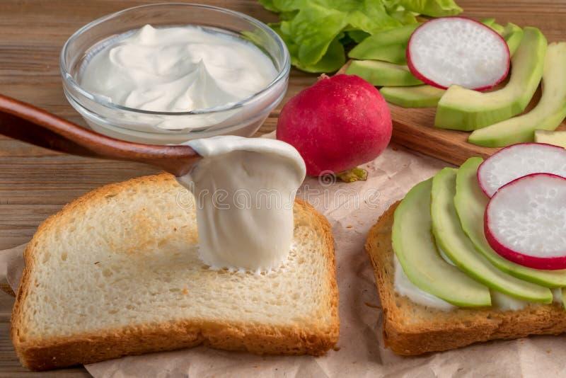 Подготовка тоста с йогуртом, авокадоом и редиской конец вверх сфокусируйте мягко стоковое изображение