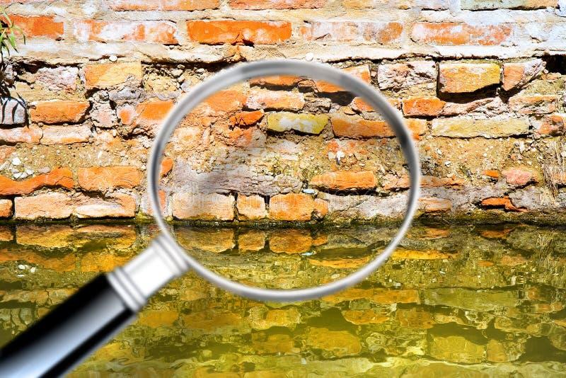 Поднимая сырость на кирпичной стене в канале вполне воды - изображения концепции увиденного через лупу стоковое изображение rf