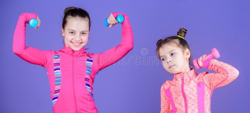 Подходящие cuties Небольшие девушки наслаждаются тренировкой фитнеса с весами Милые сестры делая тренировки фитнеса спортзала с г стоковая фотография