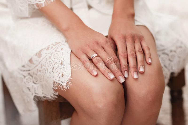 Подрезанный конец фото вверх по невесте сидя на стуле в сетевом белом халате Утро невесты стоковое фото rf
