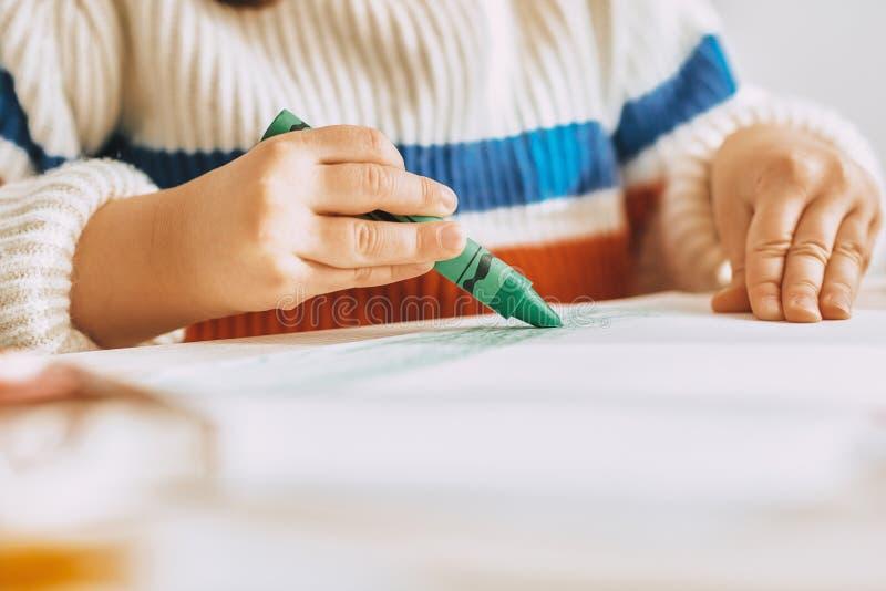 Подрезанное изображение милых красок маленькой девочки с карандашем зеленого масла сидя на белом столе дома Изображение милого pr стоковые изображения rf