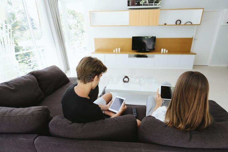 Подростки используя ПК планшета на кресле стоковое фото
