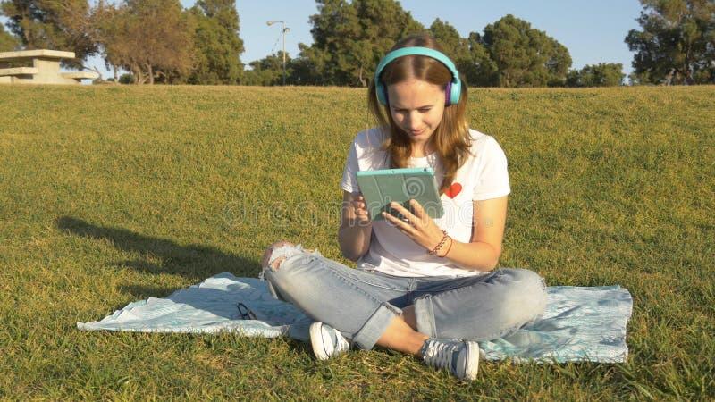 Подростковая работа с планшетом в парке стоковые фото