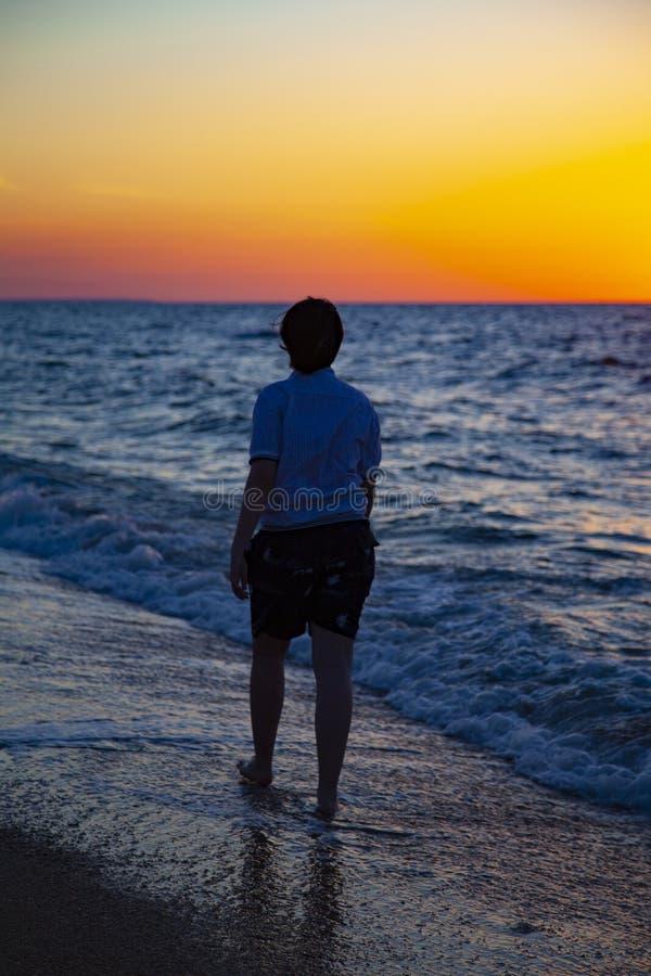 Подросток идя вдоль seashore на заходе солнца стоковое фото rf