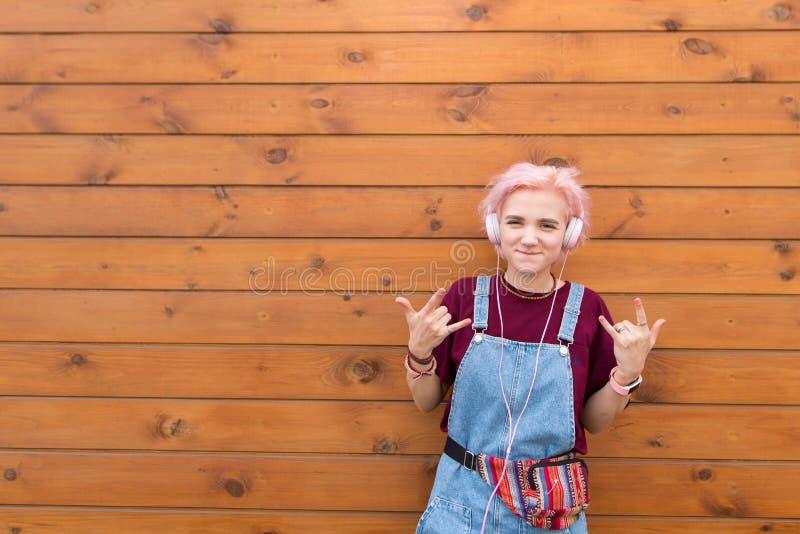 Подросток слушает для того чтобы тряхнуть в наушниках на деревянной предпосылке стоковые фото