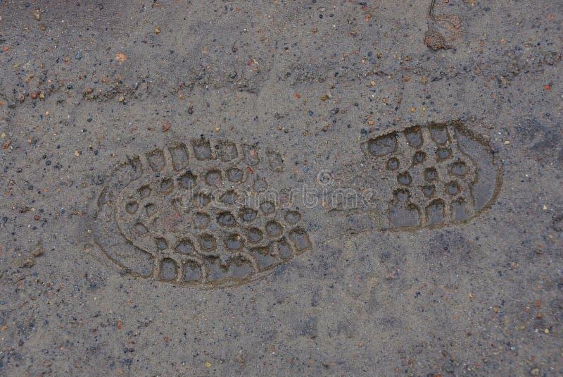 Подошвы отпечатка ботинок на влажной коричневой земле стоковые изображения