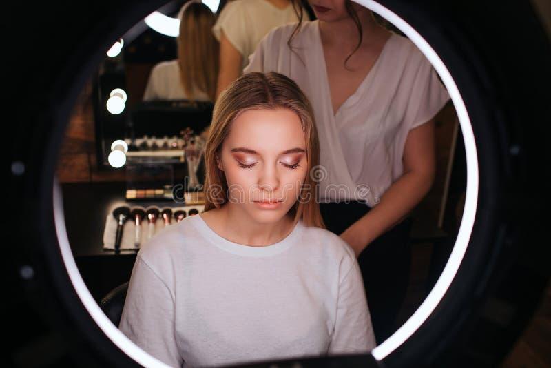Посмотрите в зеркале Молодая белокурая женщина держит глаза закрытый Она имеет тени для век на eyeline Стойка парикмахера за ей и стоковые изображения rf