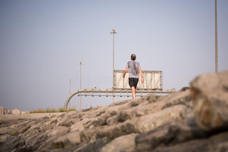 Потный человек jogging около карниза улицы Salam, Абу-Даби стоковые фотографии rf