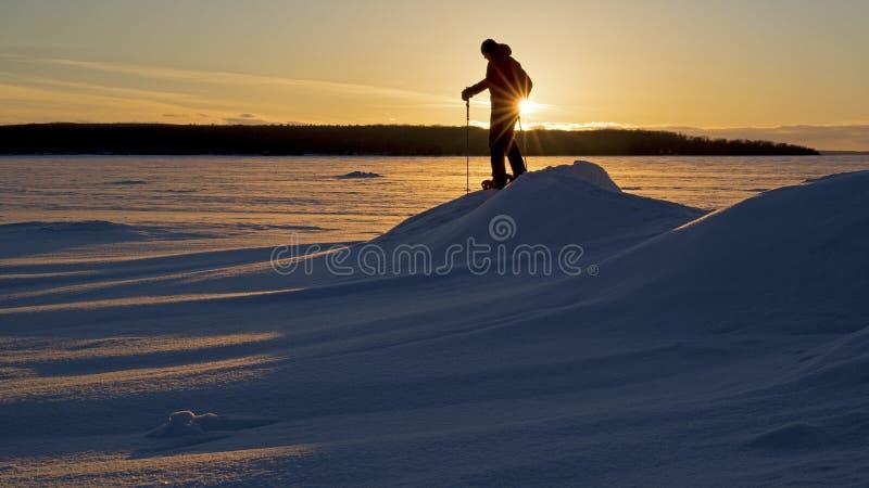 Поход Snowshoe захода солнца на замороженном озере стоковая фотография rf