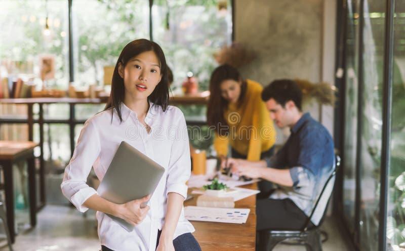 Портрет азиатской женщины с командой деятельности дела ноутбука стоковая фотография