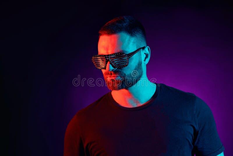 Портрет бородатого серьезного человека на студии Модель высокой моды мужская в красочных ярких неоновых светах представляя на чер стоковое фото rf