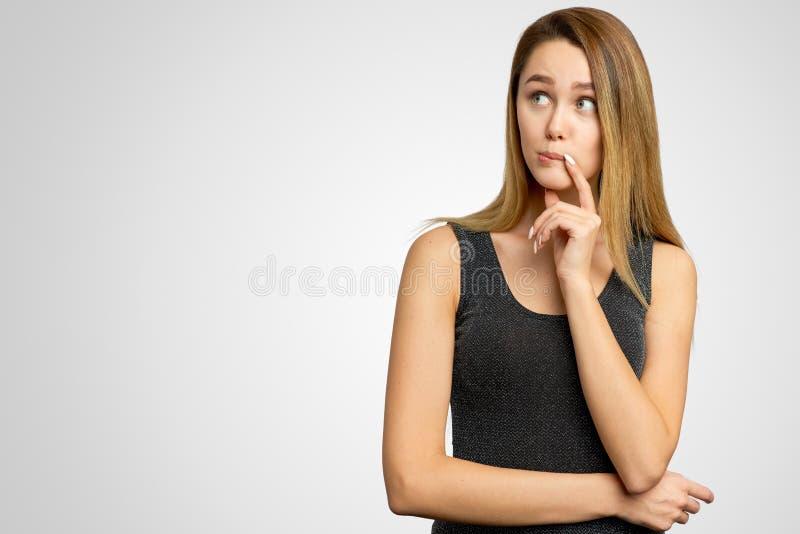 Портрет внимательной озадаченной женщины смотрит с задумчивым мечтательным выражением в сторону, думает какое решение, который ну стоковая фотография rf