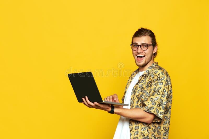 Портрет возбужденного молодого человека в eyeglasses держа ноутбук и смеясь радостным изолированного над желтой предпосылкой стоковое изображение