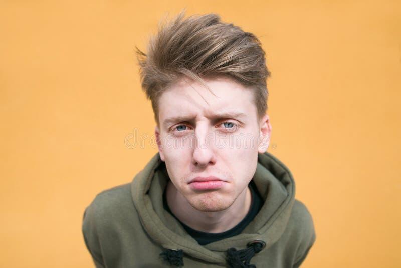 Портрет грустного молодого человека на оранжевой предпосылке Смешной парень на ярком конце предпосылки вверх стоковое фото