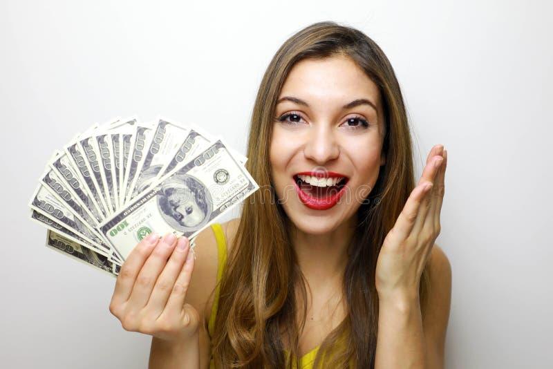 Портрет жизнерадостной милой девушки смотря камеру с пуком банкнот денег изолированных над белой предпосылкой стоковые фотографии rf