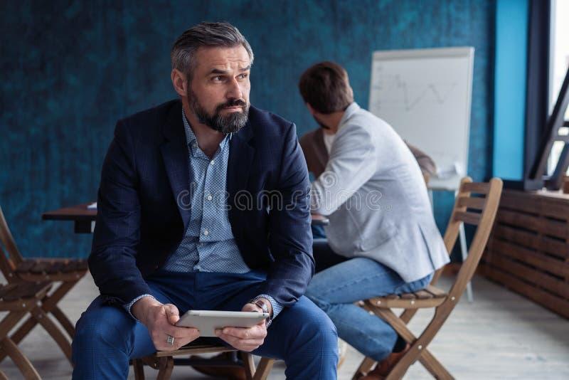 Портрет зрелого бизнесмена работая в офисе стоковые фото