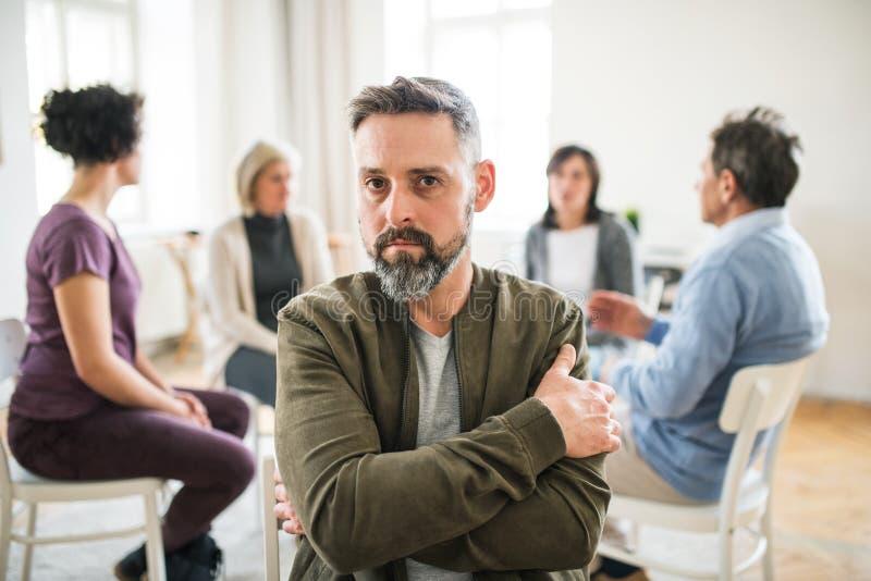 Портрет зрелого сердитого человека во время терапии группы стоковые изображения rf